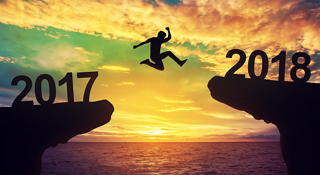 Person jumping from one cliff on the left to another on the right with a sunset over the ocean in the back ground. Left cliff has 2017 on it, right cliff has 2018 on it