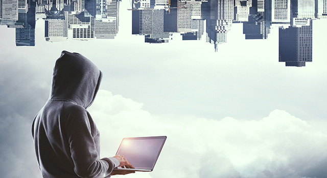 Hooded figure holding a laptop looking at the image of a city that's flipped upside down.