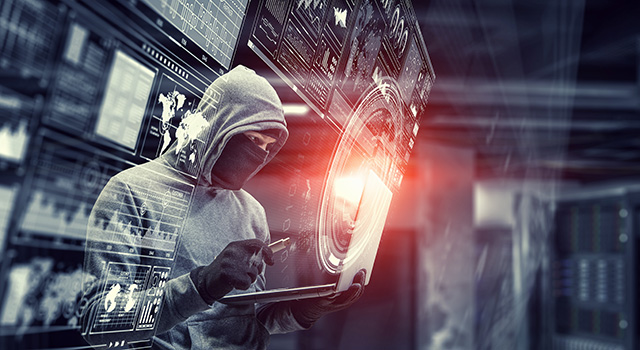 Hooded and masked man holding a USB and a laptop with hologram imagery around him