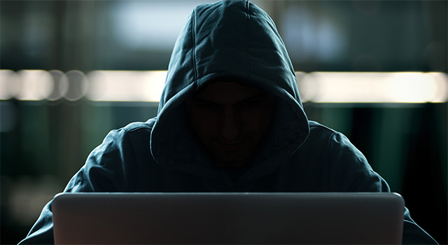 Hooded figure facing front looking at a laptop