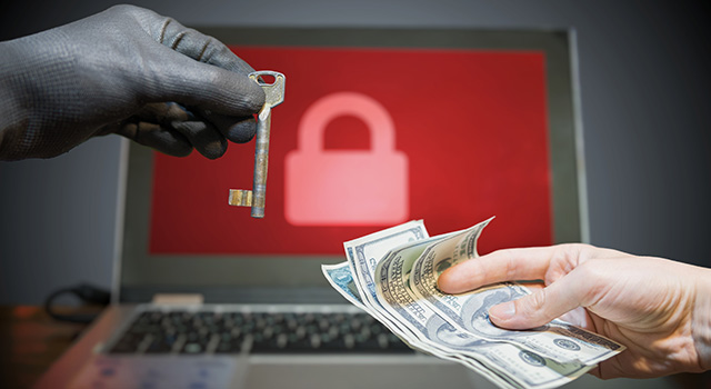 A gloved hand passing a key to an ungloved hand that is holding money. A laptop with a padlock on the screen is in the background.