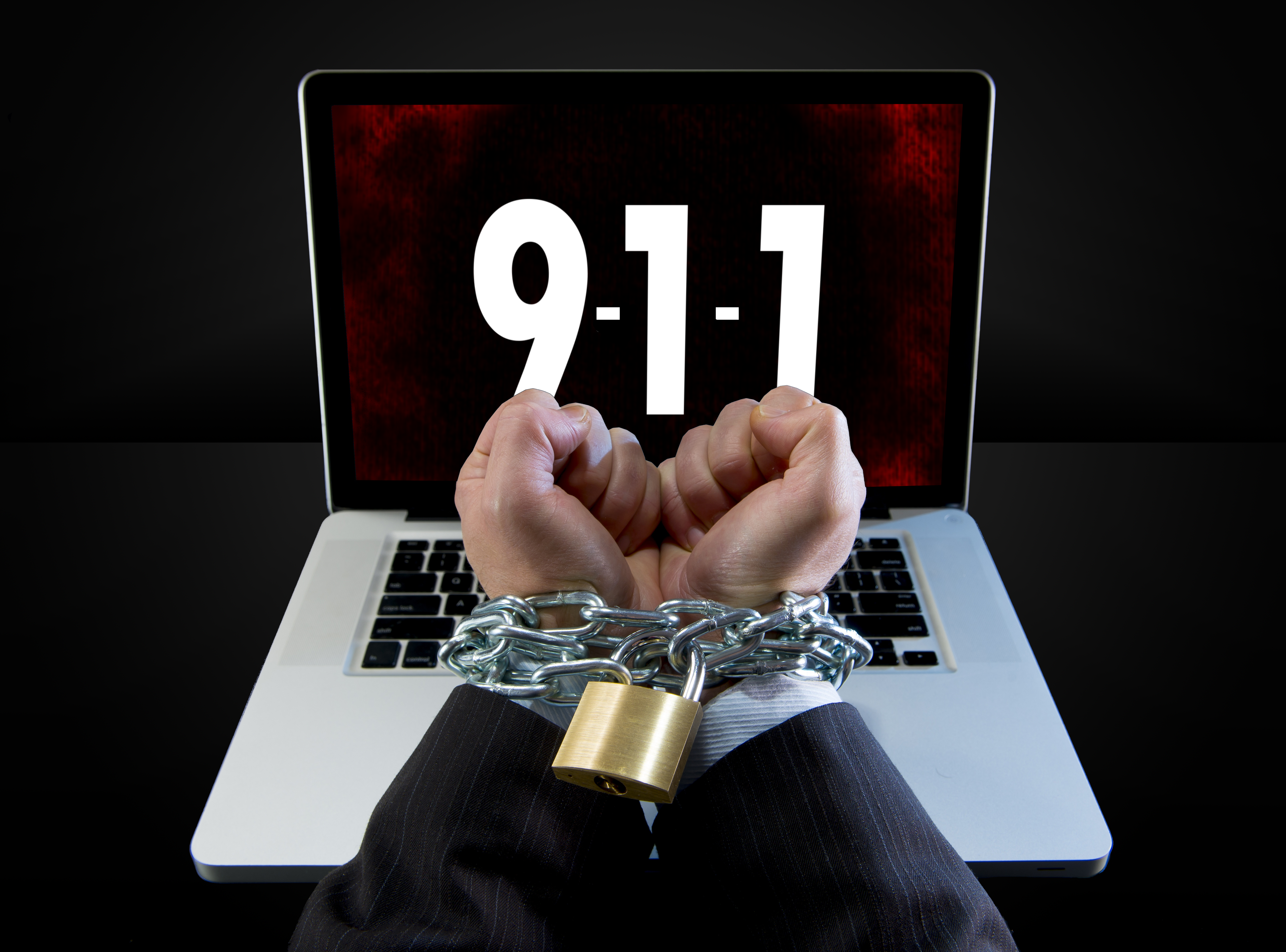 Hands shackled in front of a laptop with 9-1-1 on the screen with a menacing background.