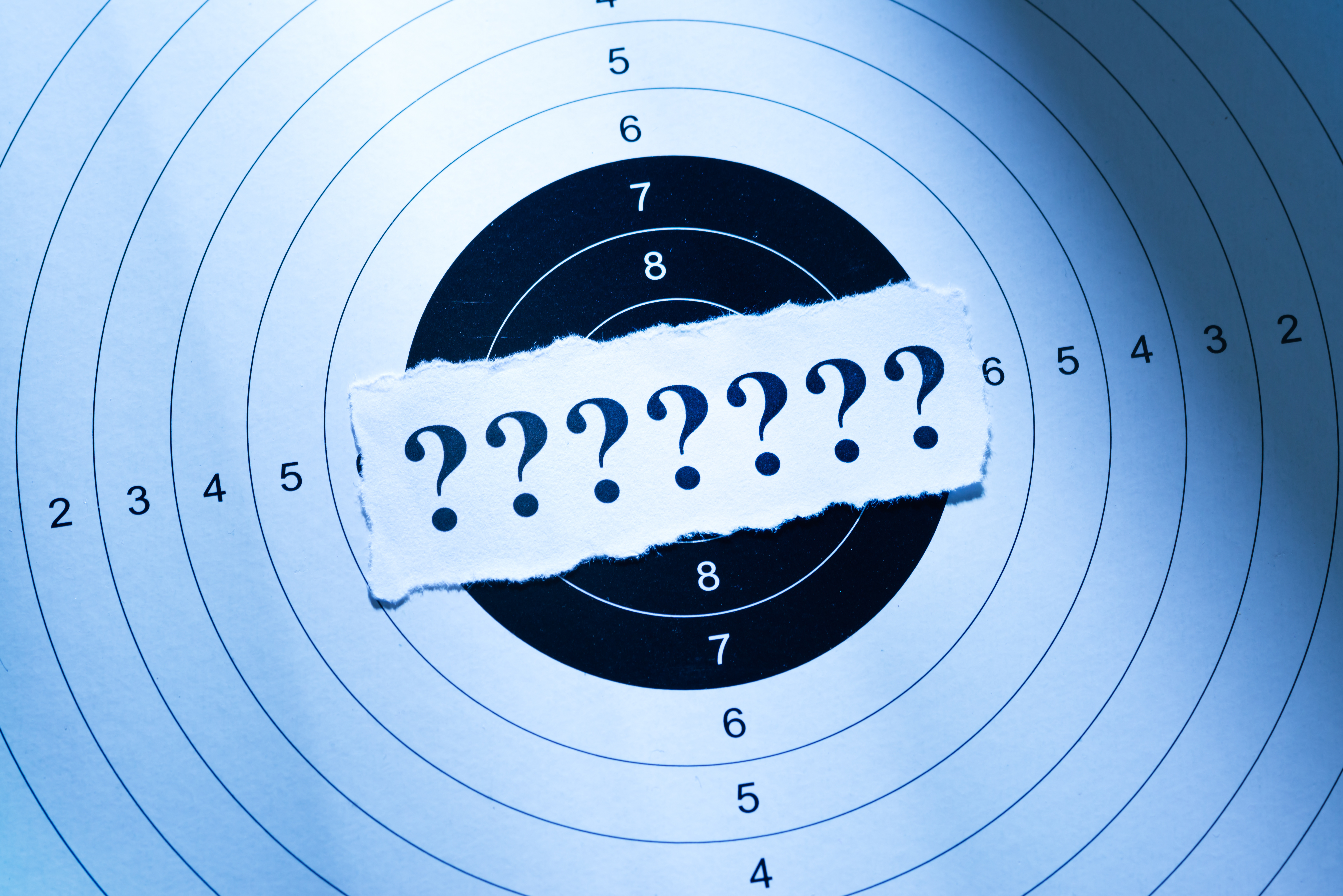 Seven consecutive question marks taped over a circular target.